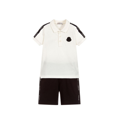 The polo shirt has black logo stripes on the shoulders and a rubberised logo patch on the chest. The shorts have matching logo stripes on the sides and an elasticated waist.
