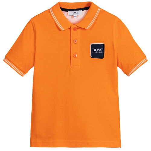 Boys orange polo shirt by BOSS. In a classic style, it is made from soft cotton piqué with a ribbed collar and a navy blue logo on the chest.