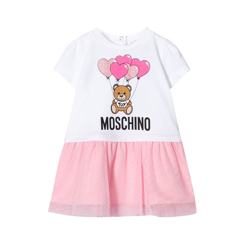 Pink and white cotton dress for little girls by Moschino Baby. Made in soft and stretchy cotton jersey, it has a bold black logo printed on the front with the brand's signature beige teddy bear and glittery pink balloons. There are poppers on the back and the pink skirt has a soft, pleated tulle overlay.