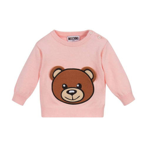 Adorable pink sweater for little girls by Moschino Baby, in a softly knitted cotton and wool blend. It has a brown Moschino Teddy Bear logo appliqué with 3D ear flaps on the front. There are useful button fastenings on one shoulder.