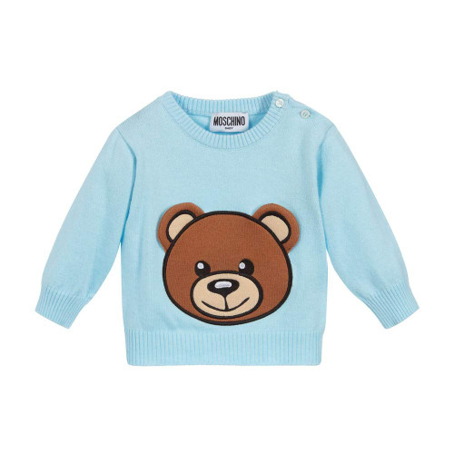 Adorable pale blue sweater for little girls and boys by Moschino Baby, in a softly knitted cotton and wool blend. It has a brown Moschino Teddy Bear logo appliqué with 3D ear flaps on the front. There are useful button fastenings on one shoulder.