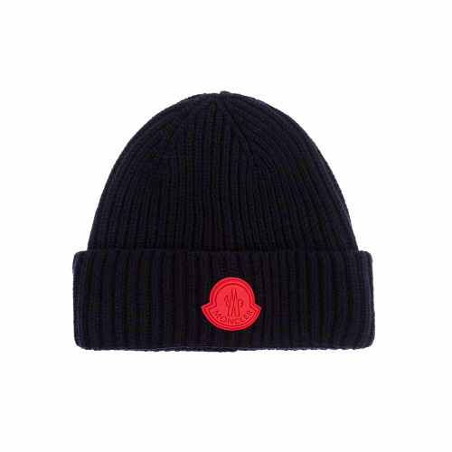 Boys navy blue Mini-me hat by French luxury brand Moncler Enfant. Knitted from soft virgin wool with chunky ribs, it has a red rubber logo patch on the brim.