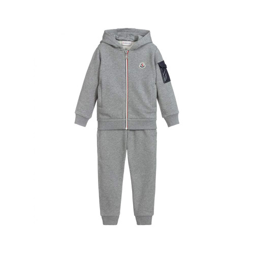 Boys black hooded, zip-up tracksuit from luxury brand Moncler Enfant. There are contrasting khaki green silky pockets and the iconic logo badges on the top and trousers.
