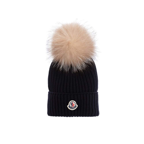Beautifully knitted from soft virgin wool, a navy blue pom-pom hat for girls by luxury brand Moncler Enfant.