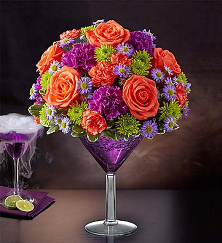 Shocktail Martini Bouquet EXCLUSIVE We're shaking things up for Halloween with our shocking cocktail creation! It's the perfect mix of vibrant orange and purple blooms inside an oversized martini glass, for a colorful, one-of-a-kind centerpiece sure to make any Halloween or seasonal celebration straight-up fun.