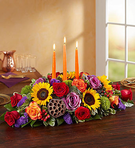 Garden of Grandeur for Fall Centerpiece Autumn gatherings call for a grand centerpiece. We've designed our luxurious arrangement with a mix of brightly-colored blooms and unique, textural accents, creating a truly unique table display. A trio of orange candles provides the perfect finishing touch, adding warmth and coziness to spirited celebrations with family an