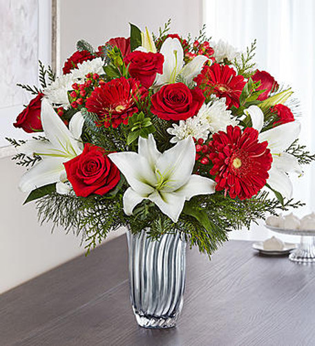 EXCLUSIVE Christmas celebrations call for bright, beautiful bouquets. Our sensational new arrangement showcases an abundance of holiday-hued blooms and lush evergreens. It's all artistically designed inside our exclusive Silver Radiance Vase with soft, silvery cascades and an elegant fluted shape. It's a radiant gift will set the tone for an elegantly festive holiday occasion.