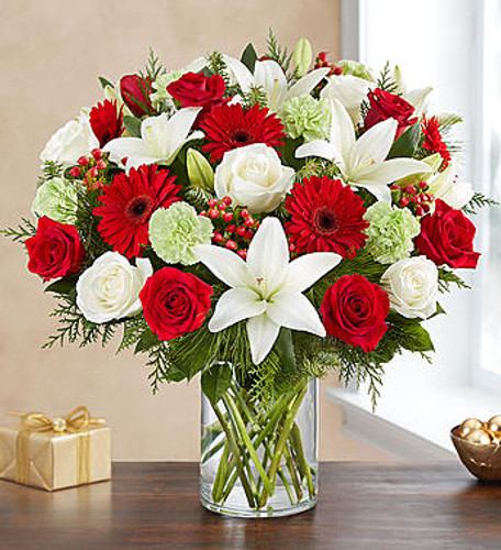 All the joyful colors of Christmas are on display in our grand holiday arrangement. An abundance of festive red and white blooms, blending contemporary style with timeless tradition. It's a beautiful gift to help friends and loved ones celebrate the season in style.