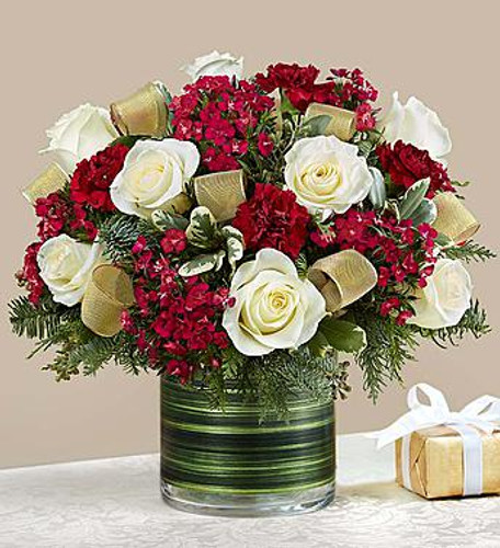 It's a glorious time of year, and there's no greater feeling than sharing the excitement with those we love. Our classic Christmas arrangement is artistically hand-designed with warm, rich burgundy & white blooms and trimmed in elegant gold ribbon. Gathered inside a clear vase lined with lush green ti leaf ribbon, this beautiful gift will fill their home with holiday spirit & style.
