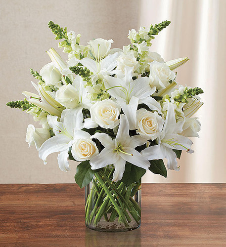 White flowers have a certain timelessness and elegance, perfect for expressing your heartfelt condolences during times of sorrow. Pristine white roses, lilies and snapdragons are hand-gathered by our florists with touches of lush greenery inside a sleek cylinder vase. It's a classic and comforting gesture that conveys the purity of your sentiment.