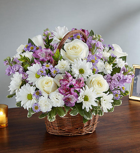 Basket arrangement of lavender stock and monte casino, purple alstroemeria and white roses, daisy poms and mini carnations; accented with fresh greenery