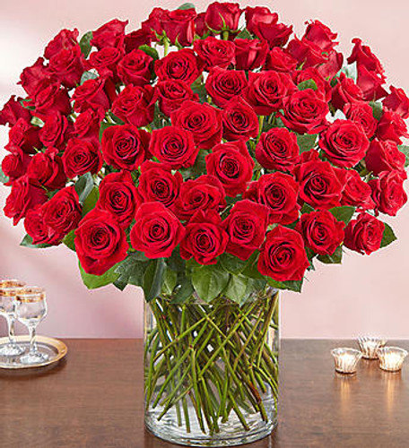 Wow the one you love like never before with 100 stunning long stem red roses! Our spectacular arrangement is artistically designed by our expert floral artisans with an abundant array of dazzling red blooms and lush greenery inside a classic cylinder vase. Standing over 2 feet tall, this luxurious surprise is personally hand-delivered for a grand romantic gesture she'll remember always.