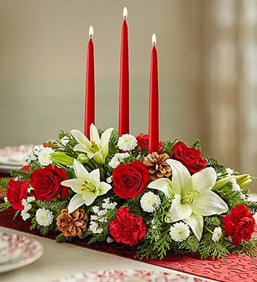 This holiday centerpiece includes 3 red taper candles, and assorted red and white flowers with holiday greenery.