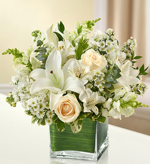 Elegant white flowers help to convey your deepest sympathies with graceful beauty that heals the soul. Our lovely cube vase arrangement offers a lasting tribute to friends and family members, crafted from fresh roses, lilies, snapdragons, monte casino and more.