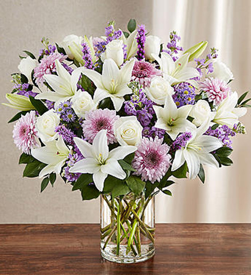 Sincerest Sorrow Lavender & White Let a deeply heartfelt sentiment be delivered in true form. Our lush, bountiful bouquet of lavender and white blooms features an elegant mix of roses, lilies and cremones, hand-designed inside a classic clear glass vase. When sent to a service or to the home of family or friends, it makes a genuinely heartwarming gesture.