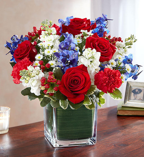 Arrangement of red roses, carnations and hypericum, white stock and monte casino and dark blue delphinium; accented with fresh greenery