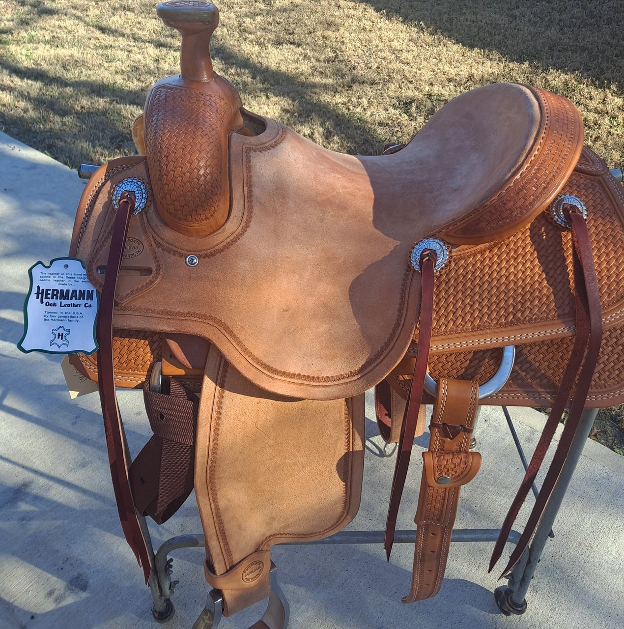 New Roping Saddle by Fort Worth Saddle Co with 14 inch seat. Hermann Oak leather. Cheyenne roll roughout seat. 6 strings. Border tooled roughout contact points. Hand tooled basket weave skirt and pommel. Gullet size is 6.75 inch, weight is 34lbs, and skirt is 26.5 inch. Made in USA. Limited lifetime warranty.  S1203
