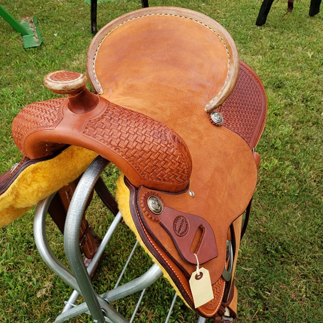 "NEW 13.5"" PLAYDAY SADDLE Got a young rider who likes play-days and trails, but doesn't want a barrel saddle? This one offers the best of both worlds... the secure deep roughout pencil roll seat and barrel stirrup performance combined with the general appearance of a buckaroo saddle. It can be as serious a saddle as they want, as it's built on a youth sized version of our Mounted Shooter tree.  Pick your own stirrups and conchos. We CAN shorten fenders if needed. Includes latigo, offside, matching leather flank billets and flank cinch, and cinch hobble.  NOT some cheap toy saddle... This is a serial numbered real leather Texas built hand tooled Fort Worth Saddle Co saddle with a US made rawhide over hardwood tree. Your young rider may someday pass it down to their own buckaroo.   Gullet size is 7 inch. Made in USA. Limited lifetime warranty.  S694"