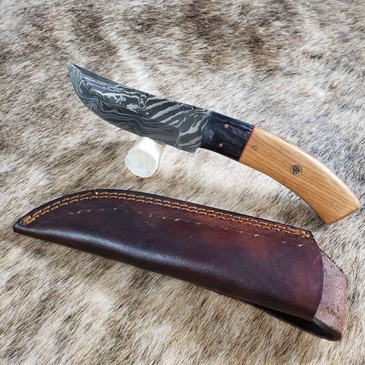 Skinner.Damascus Steel. Total length is 8 inches with 4 inch blade. Handle is Wood. Vertical  sheath included.