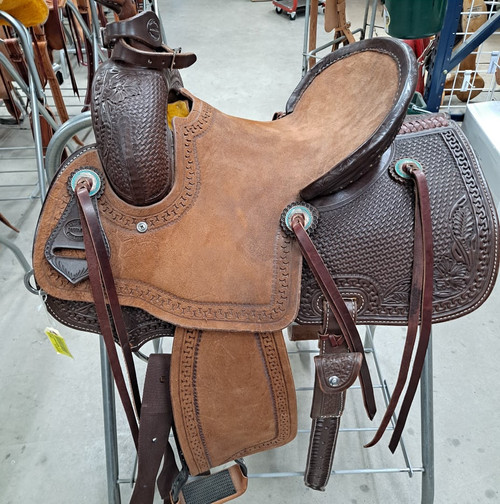 New Stock Saddle in Hermann Oak leather by Fort Worth Saddle Co with 13 inch seat. Dark chocolate coloring. Roughout seat with pencil roll. Tooled skirts. Gullet size is 7.25 inch, weight is 28lbs, and skirt is 24 inch. Made in USA. Limited lifetime warranty.  S1002