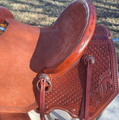 New Stock Saddle by Fort Worth Saddle Co with 13.5 inch seat. Jackson tree (hog-bars). Chestnut colored leather. Pencil roll seat. Roughout seat and fenders. Floral hand tooling on skirt and pommel. Clipped skirt. Gullet size is 7.5 inch, weight is 30lbs, and skirt is 25 inch. Made in USA. Limited lifetime warranty.  S1195