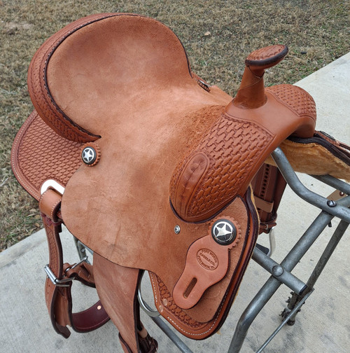 New Contender Barrel Saddle by Fort Worth Saddle Co with 14 inch seat. Built on J2 tree. Roughout contact points for secure seat. Hand-tooled skirt and pommel. Includes premium flank cinch. Comes with latigo and off-billet. Has short footprint to accommodate horses of any length. Gullet size is 6.5 inch, weight is 26lbs, and skirt is 24 inch. Made in USA. Limited lifetime warranty.  S1219