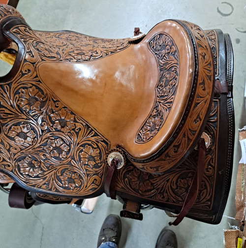 New Ranch Cutter by Fort Worth Saddle Co with 16 inch seat. Antiqued tan Hermann Oak leather. Slick seat. Extensive floral hand tooling. Matching flank and flank billets. Leather latigo and half-breed off billet. Gullet size is 7.5 inch, weight is 35lbs, and skirt is 28.5 inch. Made in USA. Limited lifetime warranty.  S1387