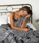 model sitting up in a bed with the weighted blanket on her lap