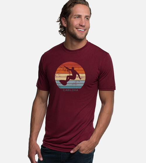 front view of model wearing red tee with sunset surfer design
