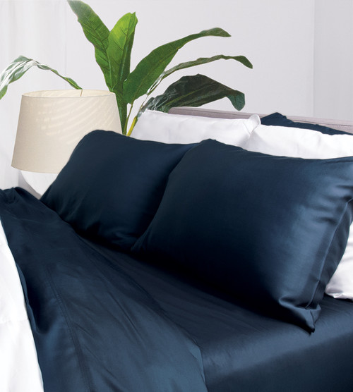 Corner shot of midnight blue be sheets showing a flat sheet, fitted sheet and two pillowcases