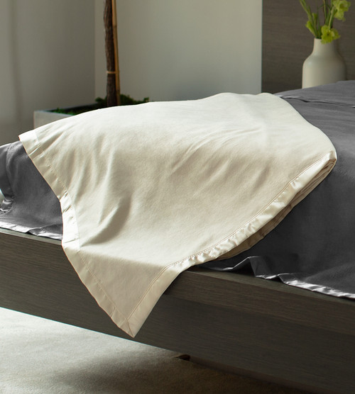 coconut milk brushed fleece blanket on the corner of a bed
