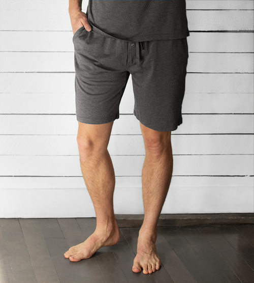 Model wearing men's charcoal heather sleep shorts with a hand in the pocket