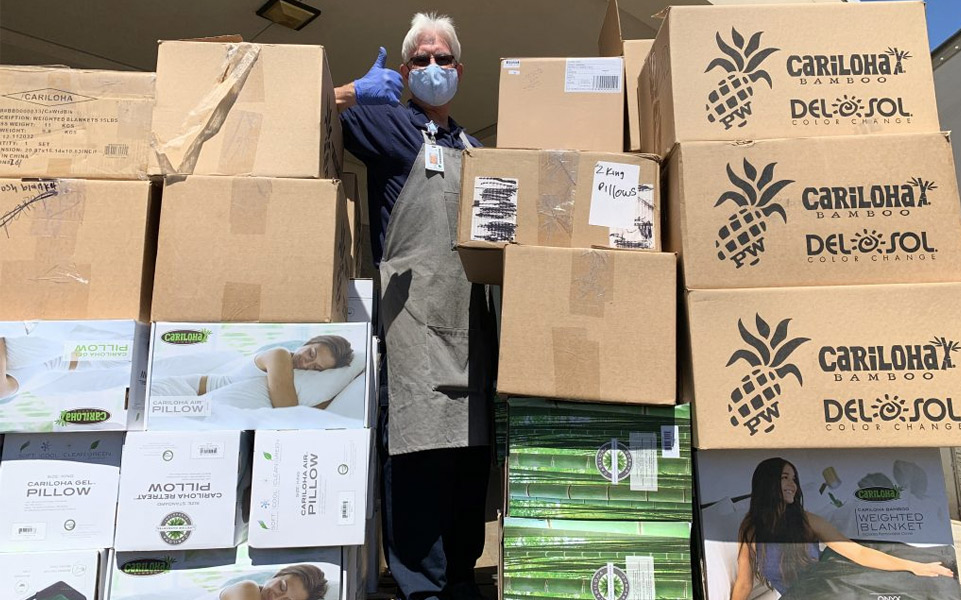 boxes of donated cariloha product and man giving thumbs up