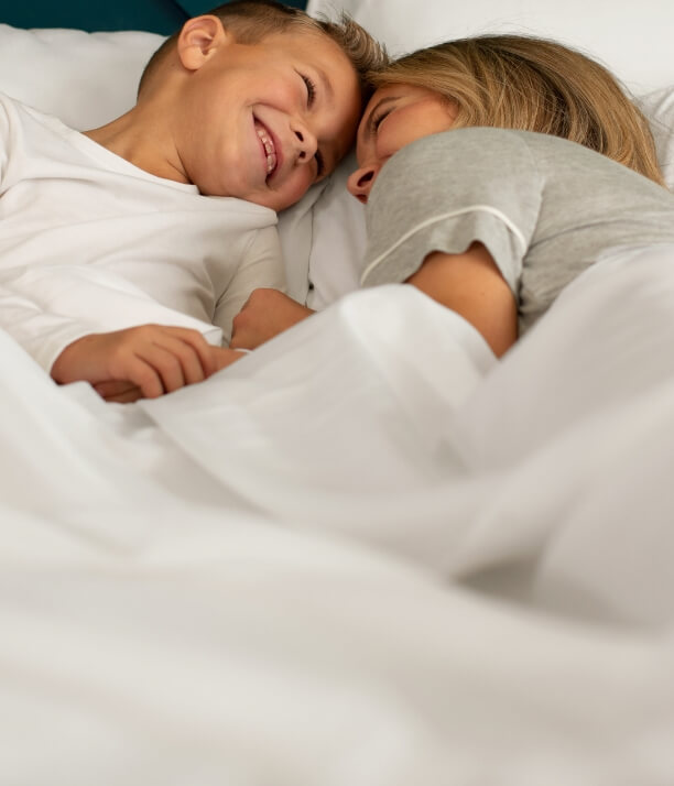 Mother and young son lying on Cariloha sheets