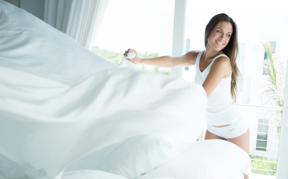 Woman making the bed with white cariloha sheets