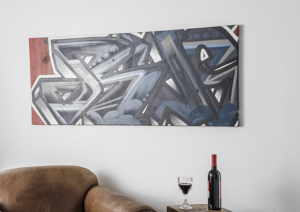 Modern urban art wall hanging design in spray painted lettering on flat steel panel.