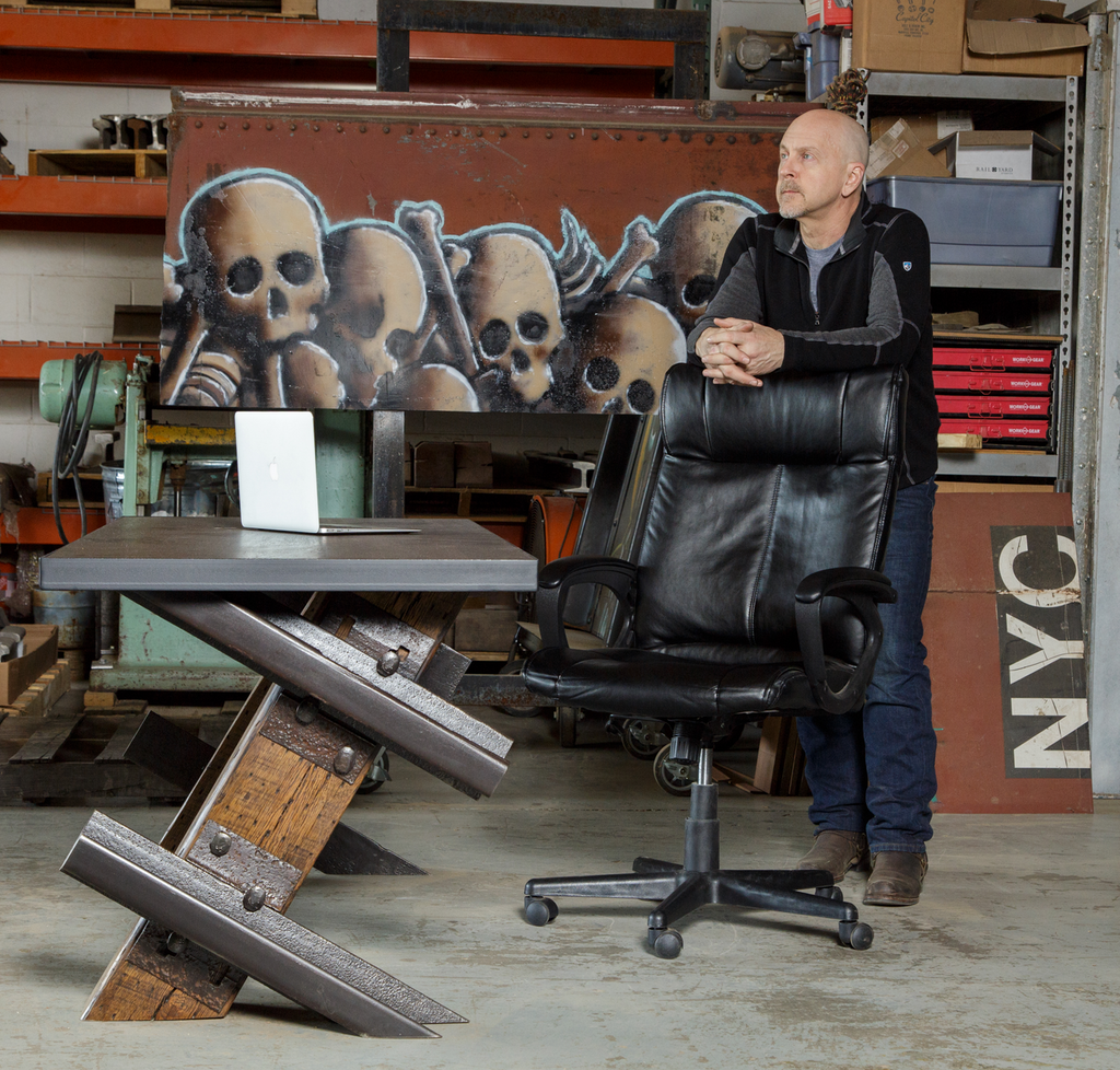 founder entrepreneur industrial designer robert hendrick with cantilever style desk in studio