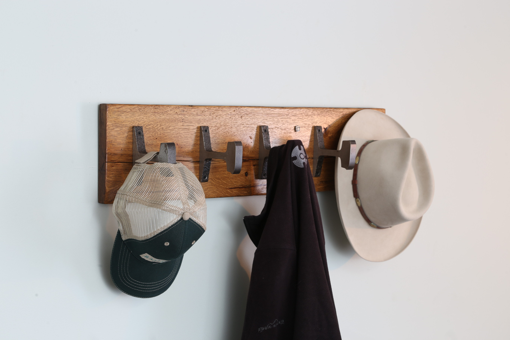natural wood finish coat rack with reclaimed steel hooks from architectural artifacts for modern industrial style commercial or residential interiors