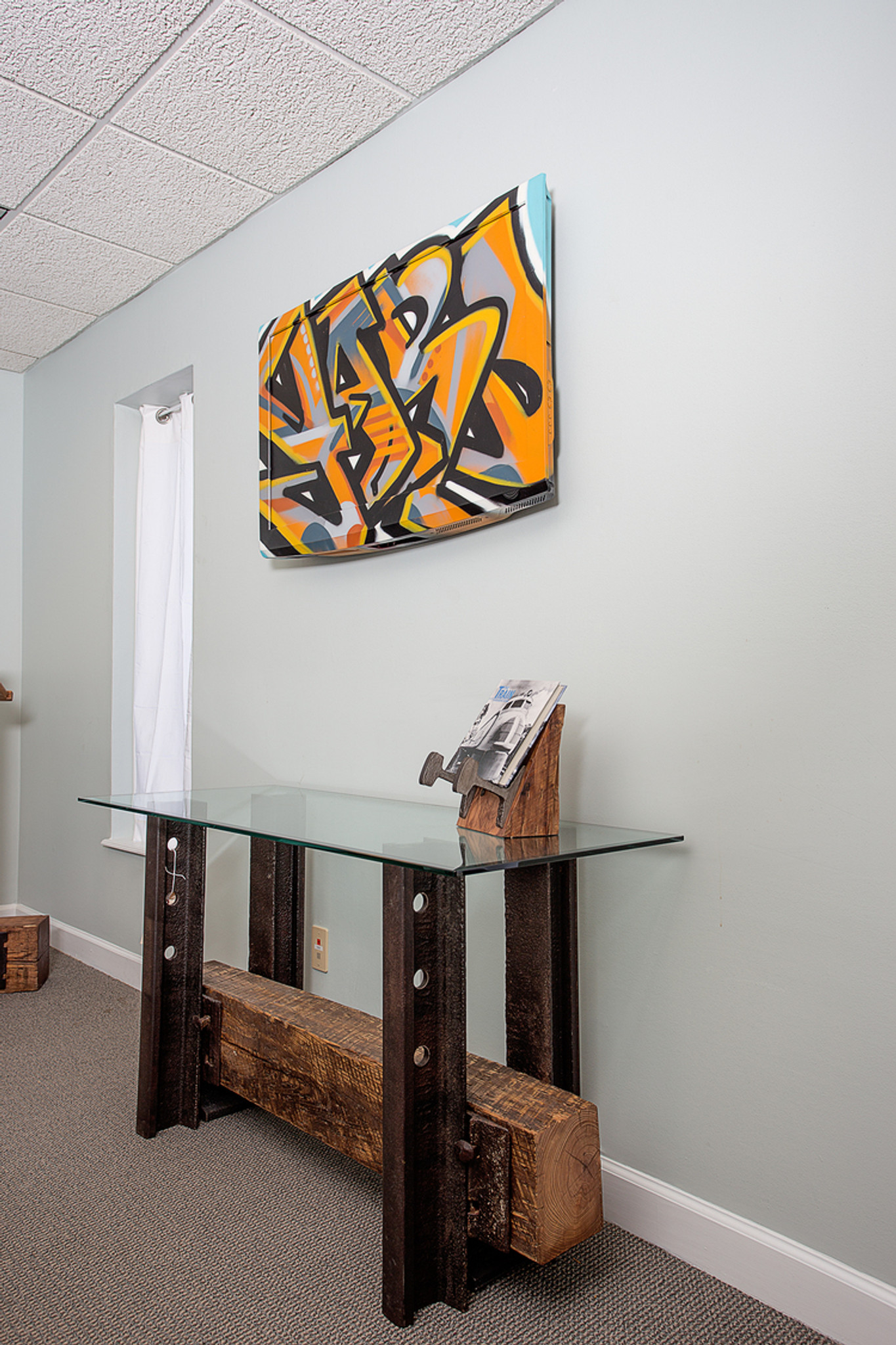 graffiti wall hanging from reclaimed materials in modern interior with salvaged material artisan table