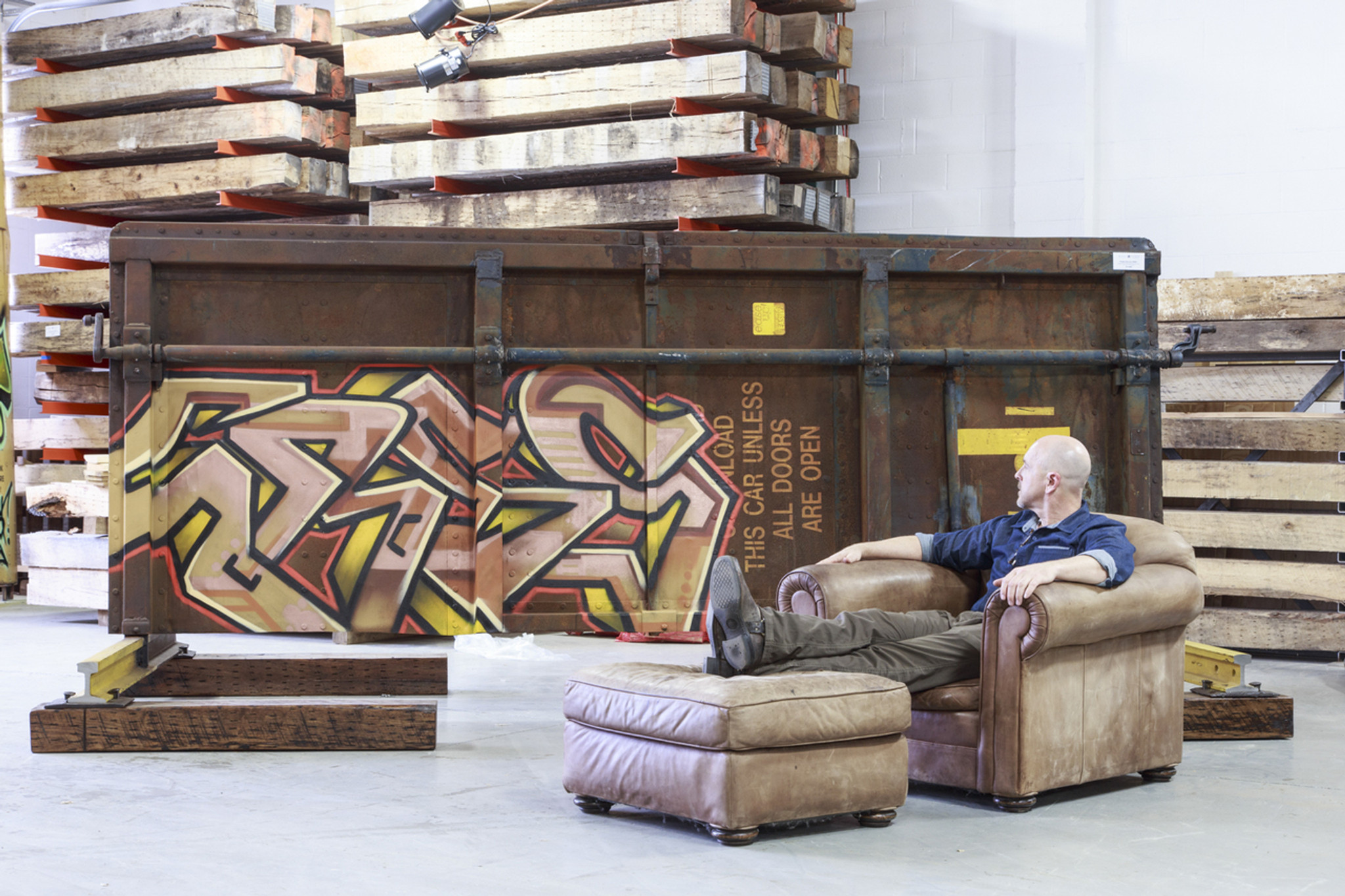 Art aficionado admiring rusted steel urban art with gold, copper and metallic lettering design