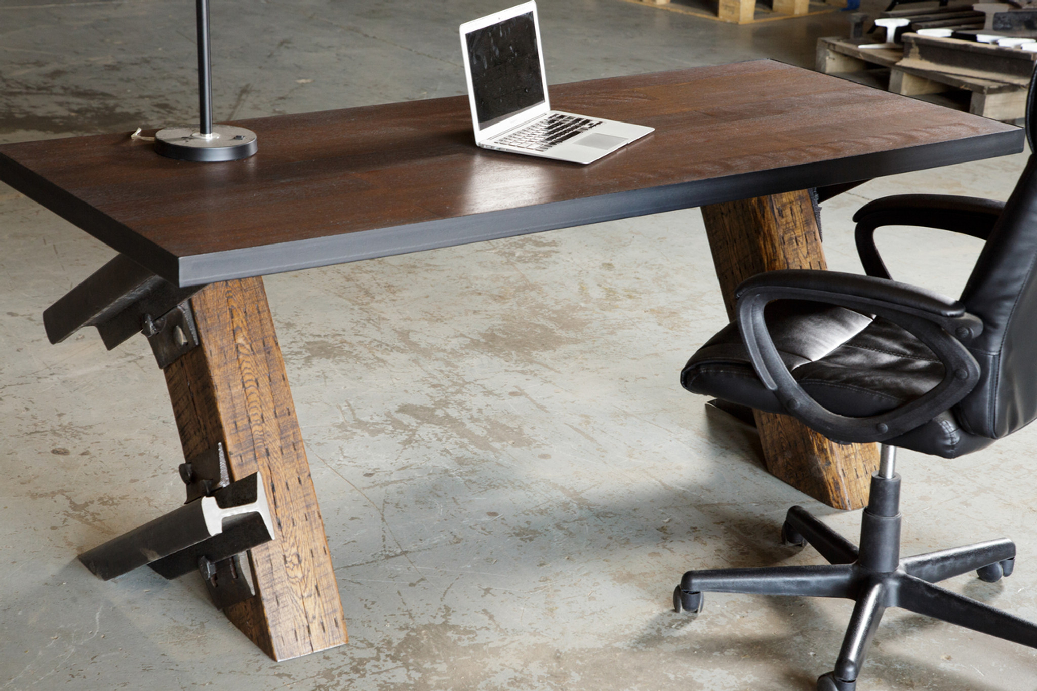 apple laptop macbook pro on industrial age style desk with cantilever legs and office chair