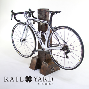 White Orbea bike on custom wood timber and steel bike stand.