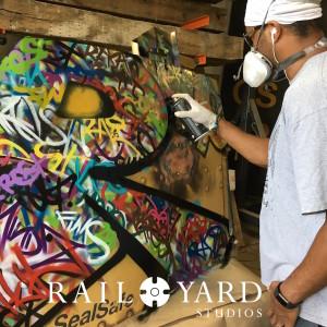 graffiti artist tagging steel railroad panel