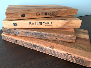 Charcuterie board from food-safe crosstie material with date nail from Rail Yard Studios
