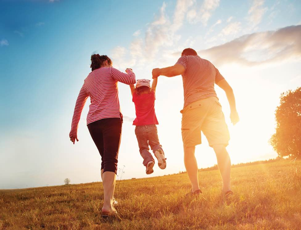 2 parents walking in a field at sunset lifting a child between them .