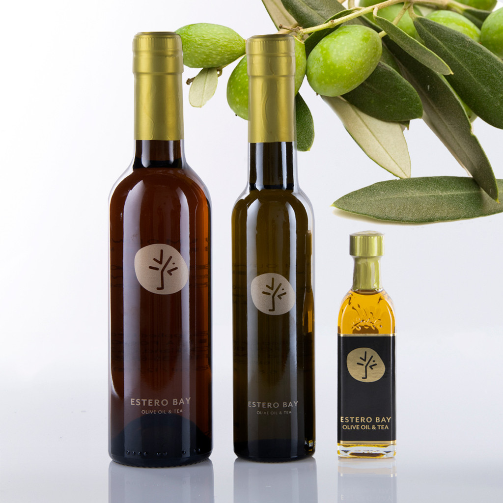 3 different size bottles of ultra premium Greek Koroneiki Extra Virgin olive oil with olive tree branch in the background.
