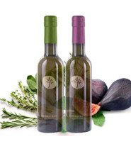 A pairing of one bottle of savory herbs de provence and one bottle of rich black mission fig balsamic with herbs and figs in the background.