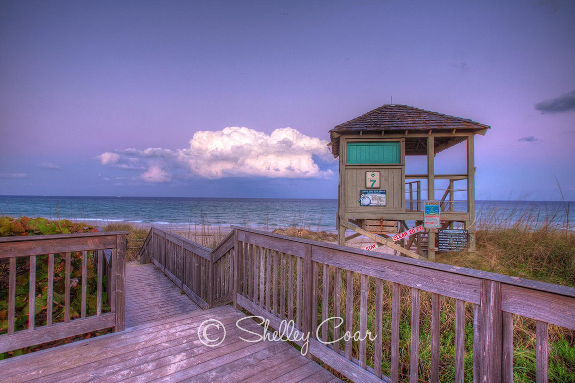 A beach sunset overlooking the Atlantic Ocean and a life guard tower at Boca Raton, Florida. Landscape photograph by Shelley Coar.