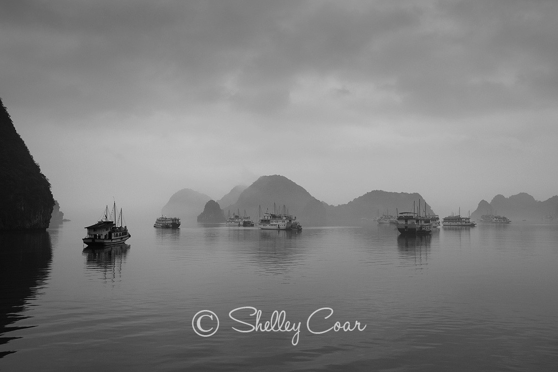 A black and white photograph of the boats of Halong Bay, Vietnam in the morning mist by Shelley Coar.