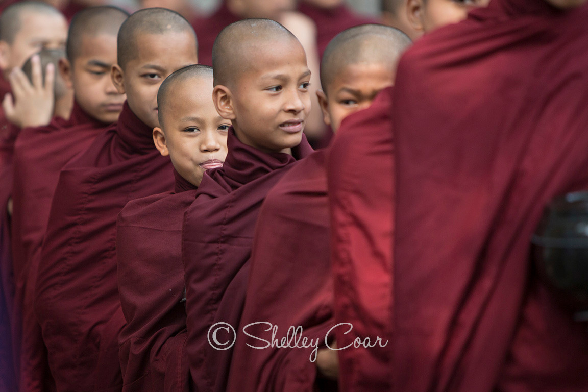 A photograph of Buddhist monks standing in line for lunch in Amarapura, Myanmar by Shelley Coar